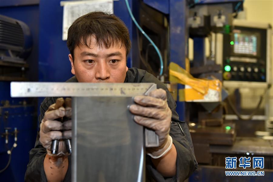 山西长治市潞安集团太阳能科技有限责任公司的工人在用工具测量单晶硅